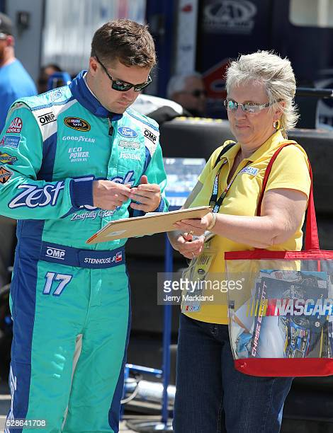 Ricky Stenhouse Jr., driver of the Zest Ford, signs an autograph before practice for the NASCAR Sprint Cup Series Go Bowling 400 at Kansas Speedway...