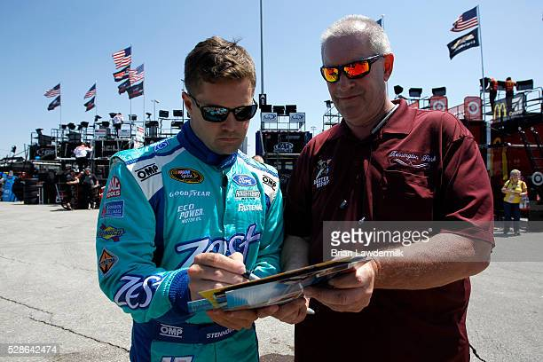 Ricky Stenhouse Jr., driver of the Zest Ford, signs an autograph during practice for the NASCAR Sprint Cup Series Go Bowling 400 at Kansas Speedway...