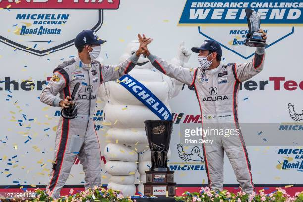 Ricky Taylor, L, and Helio Castroneves, of Brazil, celebrate after winning the Tirerack.com Grand Prix at Michelin Raceway Road Atlanta, Braselton...