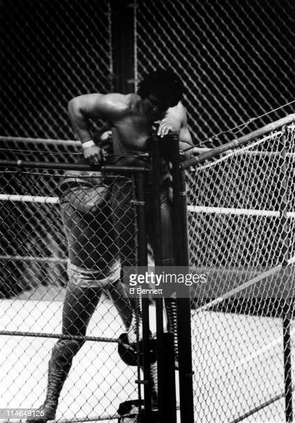 Ricky The Dragon Steamboat climbs to the top of the cage as Randy Macho Man Savage tries to pull him down during their WWF steel cage match circa 1987