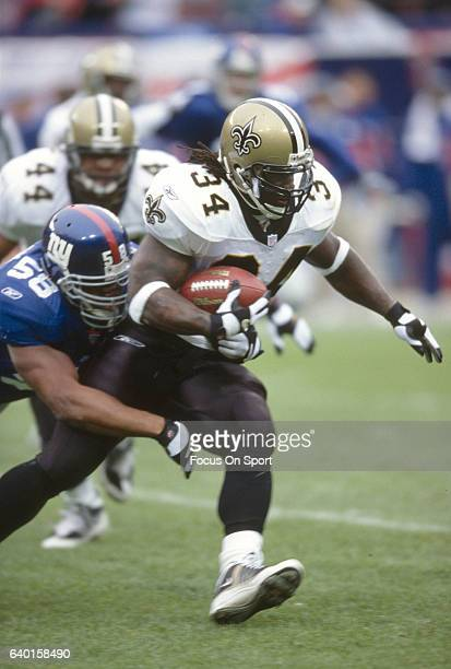 Ricky Williams of the New Orleans Saints carries the ball and gets tackled by Micheal Barrow of the New York Giants during an NFL football game...