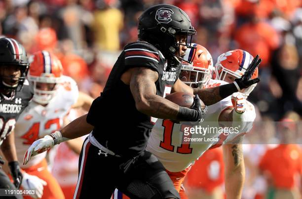 Rico Dowdle of the South Carolina Gamecocks runs with the ball against Isaiah Simmons of the Clemson Tigers during their game at WilliamsBrice...