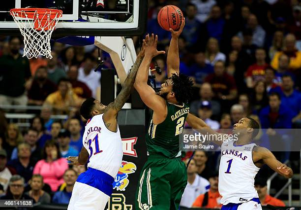 Rico Gathers of the Baylor Bears goes up against Jamari Traylor and Wayne Selden Jr. #1 of the Kansas Jayhawks in the first half during a semifinal...