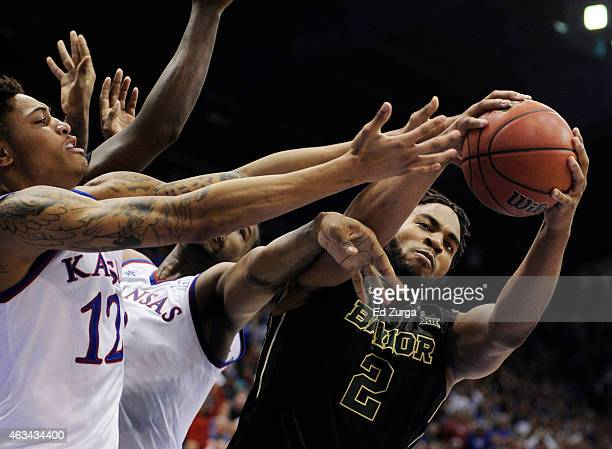 Rico Gathers of the Baylor Bears grabs a rebound from Kelly Oubre Jr #12 and Cliff Alexander of the Kansas Jayhawks at Allen Fieldhouse on February...