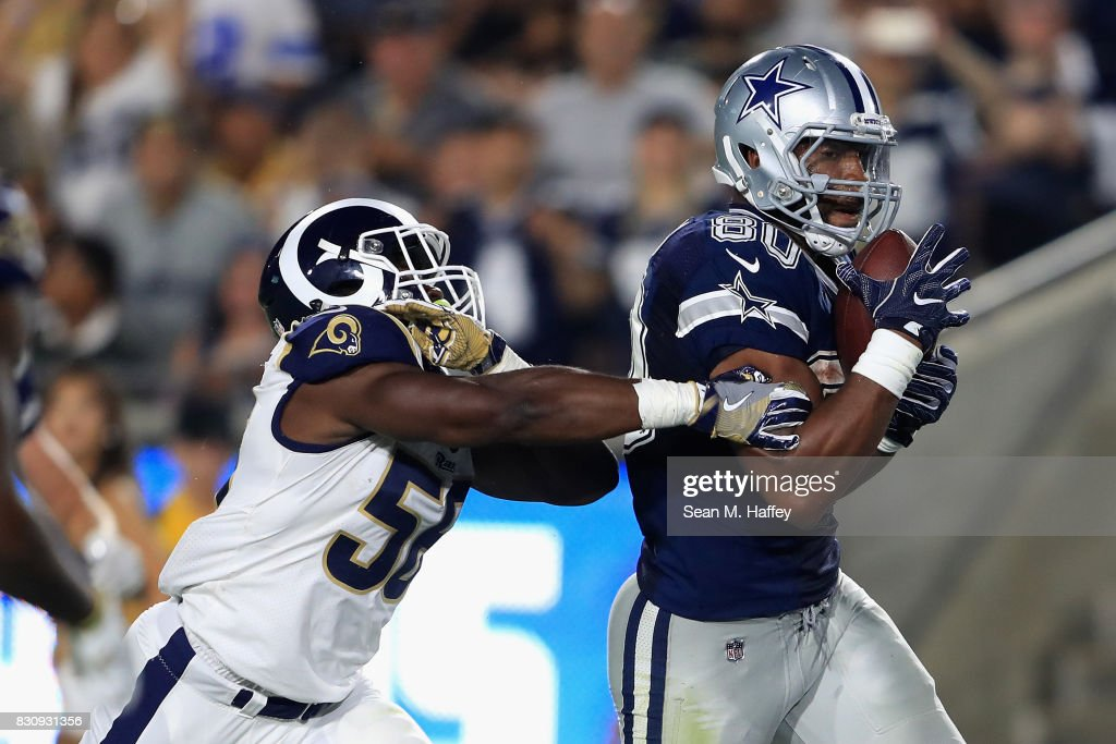 Rico Gathers #80 of the Dallas Cowboys catches a pass as Folarin Orimolade #56 of the Los Angeles Rams defends during the second half of a presason game at Los Angeles Memorial Coliseum on August 12, 2017 in Los Angeles, California.