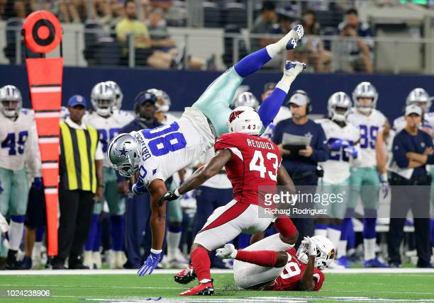 Rico Gathers of the Dallas Cowboys dives past Haason Reddick of the Arizona Cardinals for a first down in the first quarter of a preseason football...