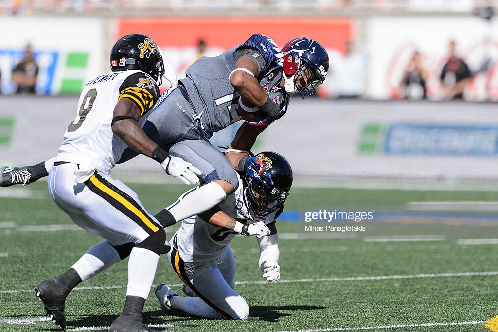 Rico Murray #0 of the Hamilton Tiger-Cats tackles Brandon London #14 of the Montreal Alouettes during the CFL game at Percival Molson Stadium on September 7, 2014 in Montreal, Quebec, Canada. The Alouettes defeat the Tiger-Cats 38-31.
