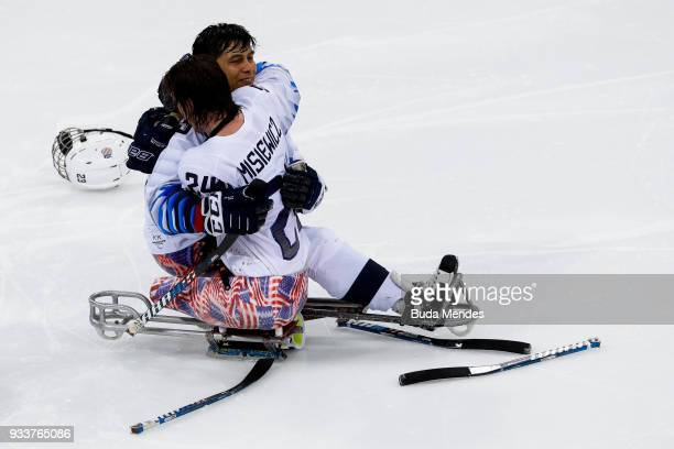 Rico Roman and Joshua Misiewicz of the United States celebrate winning the gold medal over Canada in the Ice Hockey gold medal game between United...