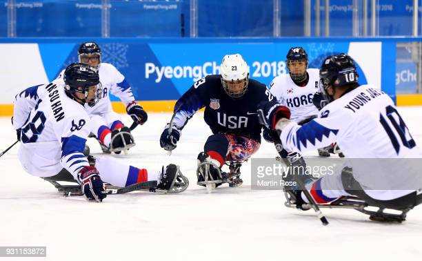 Rico Roman of United States battles for the puck with Jae Young Cho of Korea in the Ice Hockey Preliminary Round Group B game between United States...