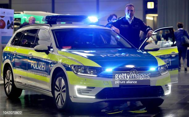 Rico Wiersig acting manager of the Leipzig police car pool stands next to a marked police hybrid vehicle car model VW Passat GTE during a conference...