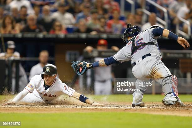Riddle of the Miami Marlins slides home safely past the tag of Jesus Sucre of the Tampa Bay Rays in the sixth inning at Marlins Park on July 4, 2018...