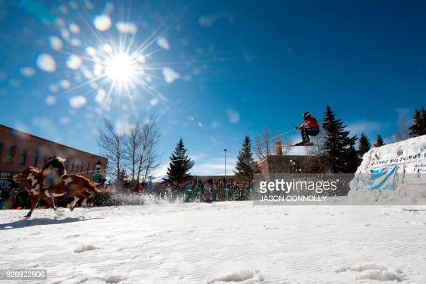 TOPSHOT Rider Amber West races down Harrison Avenue while skier Bruce Stott airs out off the final jump of the Leadville ski joring course during the...