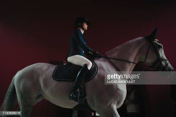 A rider and her horse enter the track prior to the 'Grand Prix Hermes' International Jumping Competition at the Grand Palais in Paris on March 24 2019