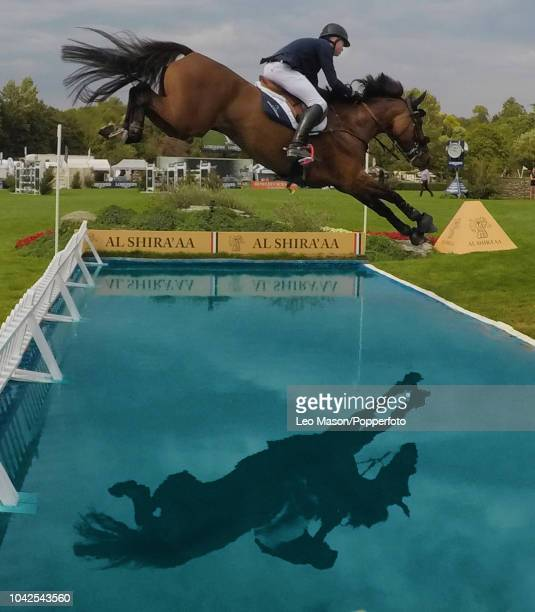 Rider and horse clear the water jump in the Longines King George V Cup International Show jumping meeting at Hickstead Show Ground on July 27 2018 in...