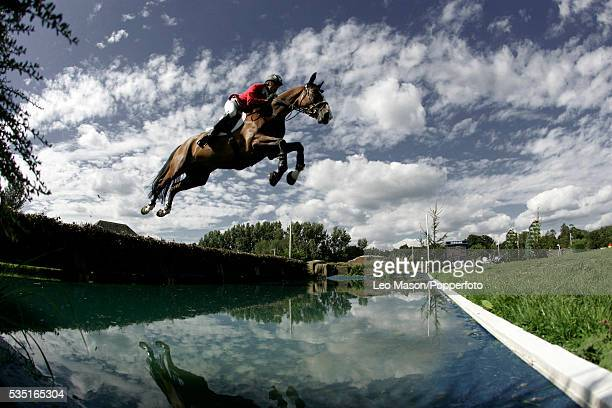 Rider and horse jumping over a lake during the Longines King George Gold Cup Hickstead Show jumping Arena Sussex on 29th July 2007.