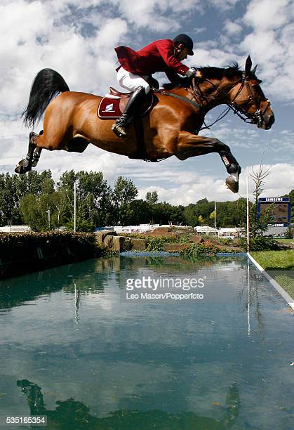 Rider and horse jumping over a lake during the Longines King George Gold Cup Hickstead Show jumping Arena Sussex.