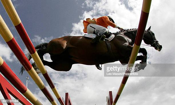 Rider and horse jumping over an obstacle during the Longines King George Gold Cup Hickstead Show jumping Arena Sussex on 27th July 2007.