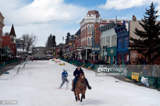 A rider and skier race down Harrison Avenue during the 70th annual Leadville Ski Joring weekend competition on March 4 2018 in Leadville Colorado...