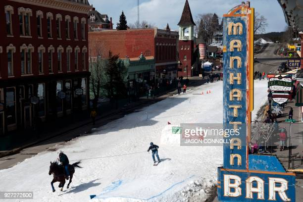 A rider and skier race past historical buildings on Harrison Avenue during the 70th annual Leadville Ski Joring weekend competition on March 4 2018...