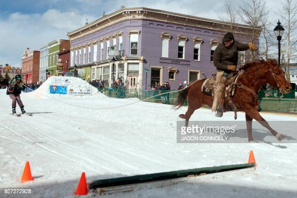 A rider and skier race to the finish line during the 70th annual Leadville Ski Joring weekend competition on March 4 2018 in Leadville Colorado...