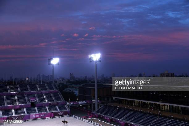 Rider attends evening training before the city skyline during the Tokyo 2020 Olympic Games at the Equestrian Park in Tokyo on July 26, 2021.