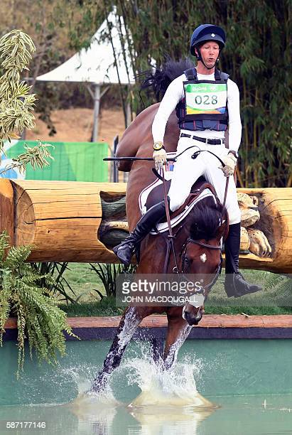 US rider Clark Montgomery on Loughan Glen stumbles into the water as he competes in the Eventing's Individual Cross Country of the Equestrian during...