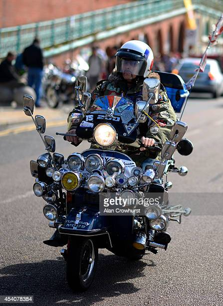 A rider cruises along the seafront during the Brighton Mod weekender on August 24 2014 in Brighton England This August Bank holiday will see many...