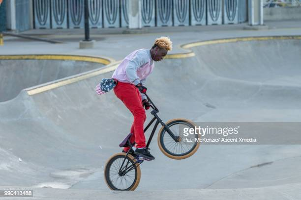 bmx rider enjoys stunt riding in urban park - cabelo oxigenado - fotografias e filmes do acervo