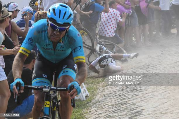 TOPSHOT A rider falls in a turn while riding through a cobblestone section during the ninth stage of the 105th edition of the Tour de France cycling...