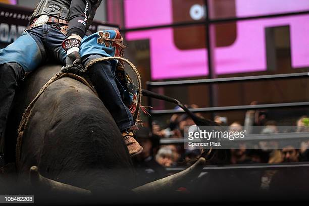 A rider hangs onto a bull in Times Square as part of the Professional Bull Riders competition on October 15 2010 in New York City PBR held a 10rider...
