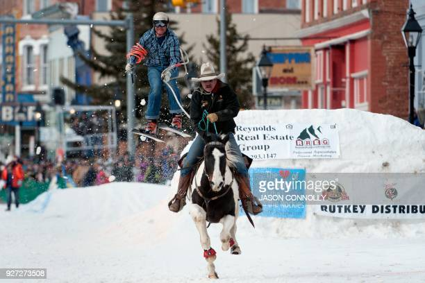 TOPSHOT Rider Jeff Dahl races down Harrison Avenue while skier and son Greg Dahl airs out off the final jump of the Leadville ski joring course...