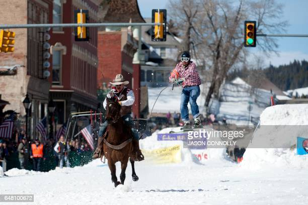 Rider Jeff Dahl races down Harrison Avenue while skier and son Jason Dahl airs out off the final jump of the Leadville skijoring course during the...