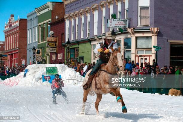 Rider Jeff Dahl races down Harrison Avenue while skier and son Jason Dahl hangs onto the tow line while racing in the 68th annual Leadville Ski...