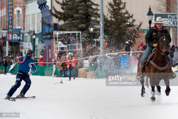 Rider Jeff Dahl races down Harrison Avenue while skier Bruce Stott reaches for the final ring while competing in the Open divison during the 70th...