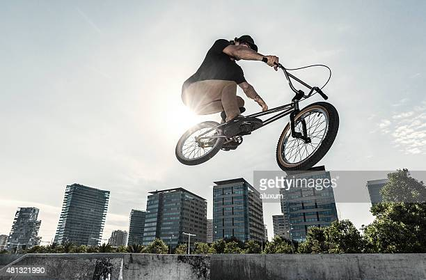 bmx rider jumping in urban environment - bmx cycling stock pictures, royalty-free photos & images