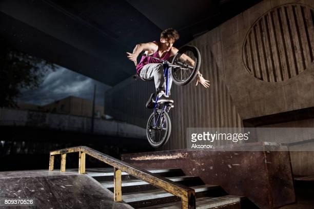 BMX rider jumping on his bike in skatepark