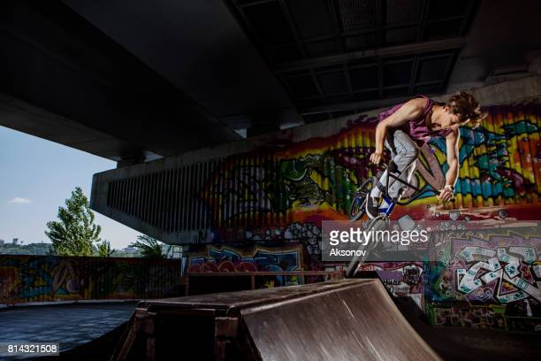 BMX rider jumping on his bike in skatepark