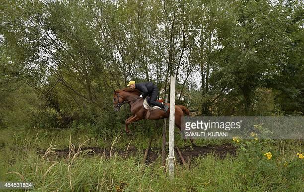 Rider jumps with his horse during a training day at Vampil yard, near Malacky, Slovakia on September 3, 2014. AFP PHOTO/SAMUEL KUBANI