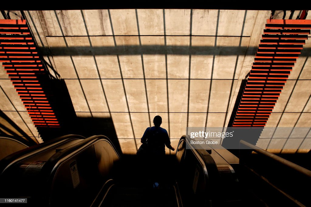 A rider makes her way down the escalator at Alewife Station to board...  News Photo - Getty Images