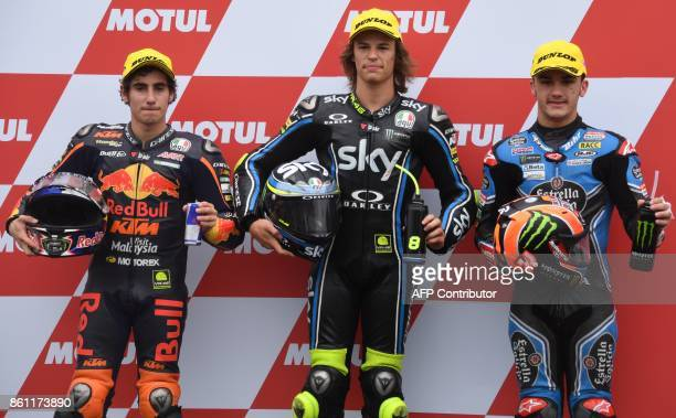 KTM rider Nicolo Gulega of Italy celebrates his Moto3class pole position while posing with second fastest KTM rider Niccolo Antonelli of Italy and...