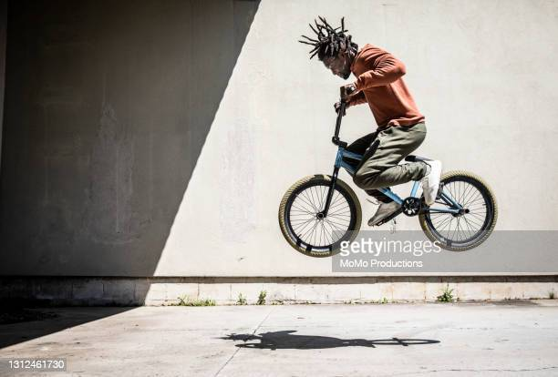 bmx rider performing jump in outdoor industrial environment - african american culture stock pictures, royalty-free photos & images