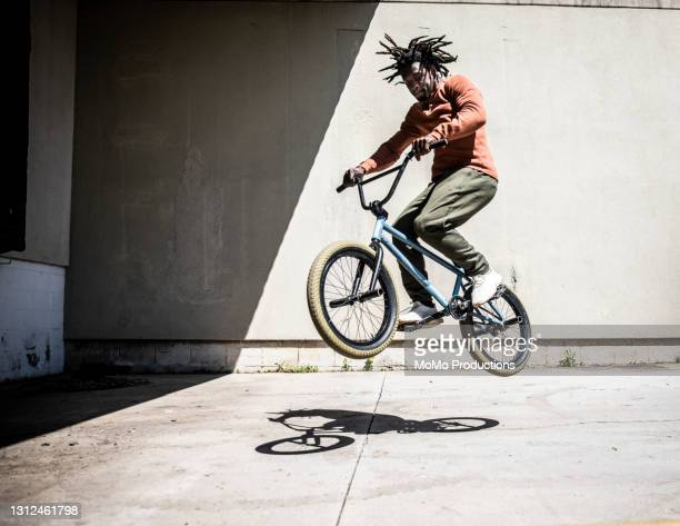 bmx rider performing jump in outdoor industrial environment - cool attitude stock pictures, royalty-free photos & images