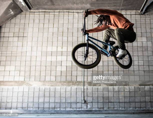bmx rider performing jump in warehouse environment - african american culture stock pictures, royalty-free photos & images