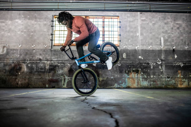 BMX rider performing trick in warehouse environment