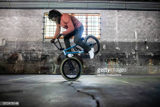bmx rider performing trick in warehouse environment - african american culture stock pictures, royalty-free photos & images