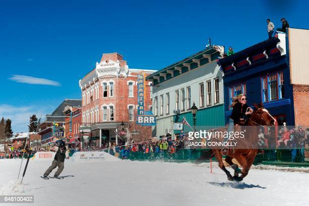 A rider races down Harrison Avenue while a skier navigates the course during the 68th annual Leadville Ski Joring weekend competition on Saturday...