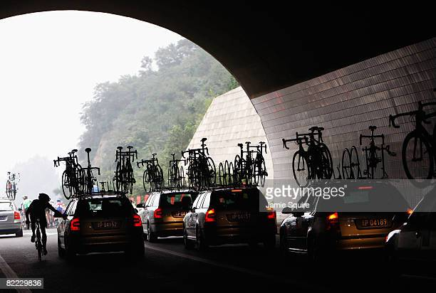 A rider takes a drink from the support car as he competes in the Men's Road Cycling event held on the Road Cycling Course during day 1 of the Beijing...