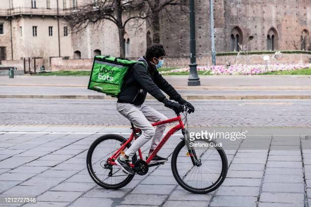 A rider with mask delivers food to Turin during on the Italy Continues Nationwide Lockdown To Control Coronavirus Spread on March 16 2020 in Turin...