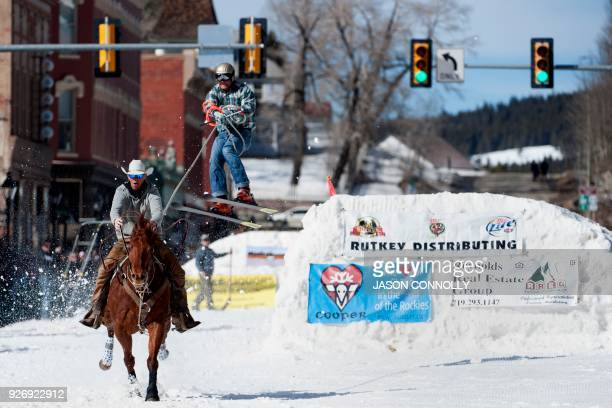 Rider Zach West races down Harrison Avenue while skier Greg Dahl airs out off the final jump of the Leadville ski joring course during the 70th...