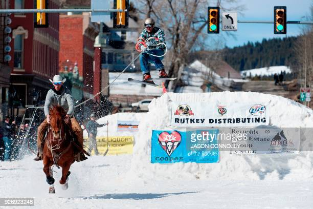 TOPSHOT Rider Zach West races down Harrison Avenue while skier Greg Dahl airs out off the final jump of the Leadville ski joring course during the...
